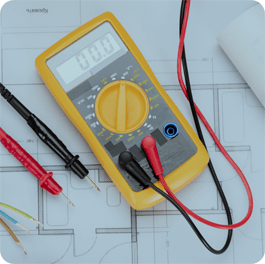 A yellow voltmeter with red and black cables connected to it sitting on a blueprint